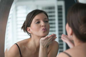 09 Apr 2004 --- Woman Blowing Herself a Kiss in the Mirror --- Image by © Larry Williams/CORBIS